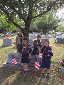 Cubs putting flags on grandfathers grave